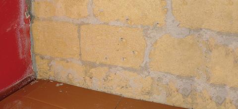 """Scrostare la fascia bassa dell'intonaco compromessa da efflorescenze e distacchi e portando il muro  """"a vivo"""""""